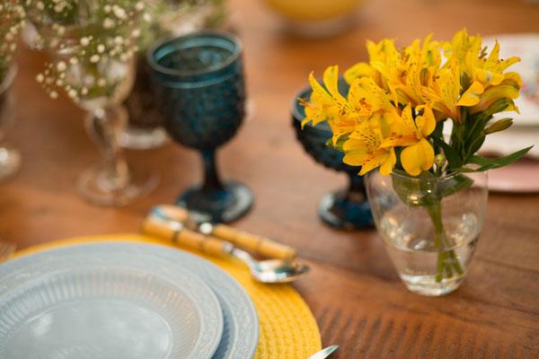 Mesa posta café da manhã em tons de azul e flores amarelas
